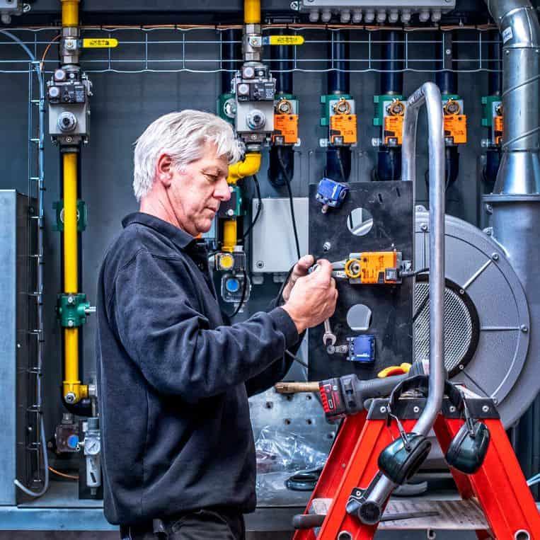 Ben monteur van DFW bij een crematieoven die nog op gas werkt.